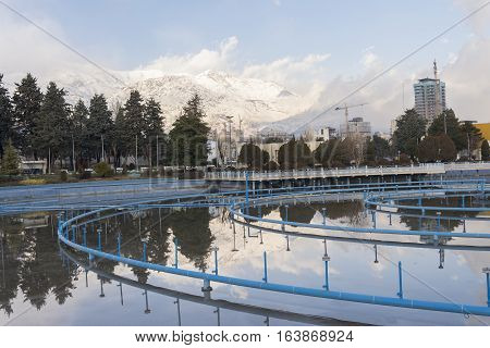 Tehran International Permanent Fairground Pool with Off Fountains Landscape Cityscape of Tehran and Alborz Mountains Covered by Snow at Background.