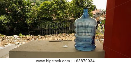 A gallon of water on top of a brick wall near red pillar photo taken in Semarang Indonesia java