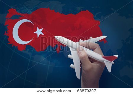 hand holding airplane with map of Turkey.