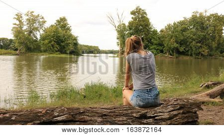 A beautiful girl sits and watches as a river slowly flows past.