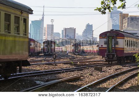 Railway train on the railroad tracks in Bangkok station. Many people in Thailand popular travel by train because it is cheaper.