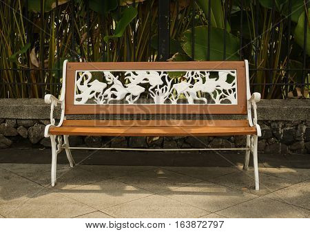 a bench made from wood and metal engraving white coloured photo taken in Semarang Indonesia java