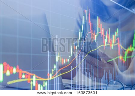 graph chart of stock market. background business girl using smart phone and laptop on wood desk in office.