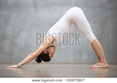 Beautiful young woman with tattoo on foot meaning Wild cat working out in white sportswear against grey wall, doing yoga or pilates exercise. Downward facing dog, adho mukha svanasana. Full length