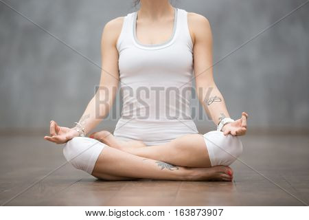 Front view portrait of beautiful young woman with floral tattoos working out against grey wall, resting after doing yoga exercises, sitting in Ardha Padmasana, Lotus pose, relaxing. Close up