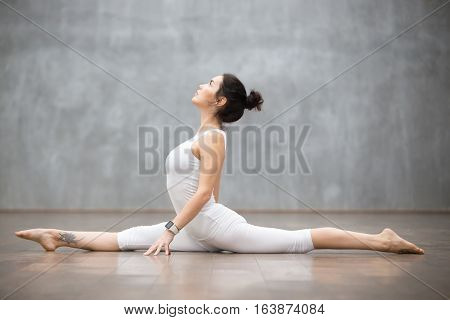 Beautiful young woman wearing white sportswear set and smartwatch working out against grey wall, doing yoga or pilates exercise. Monkey god, splits, hanumanasana. Full length