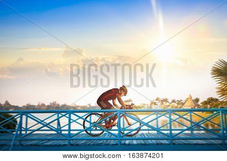 Man riding mountain bike on bridge trail at sunrise.