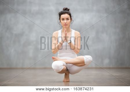 Young calm pretty woman wearing white sportswear working out against grey wall, doing yoga or pilates exercise. Sitting in squat position, Half Lotus Toe Balance, variation of Utkatasana. Full length