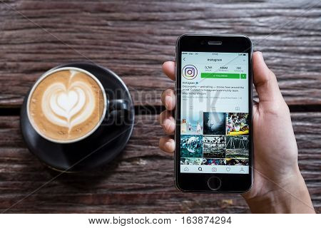 CHIANG MAI THAILAND - OCT 242016: A women holds Apple iPhone 6S with Instagram application on the screen with latte hot coffee cup on wood desk in coffee shop. Instagram is a photo-sharing app for smartphones.
