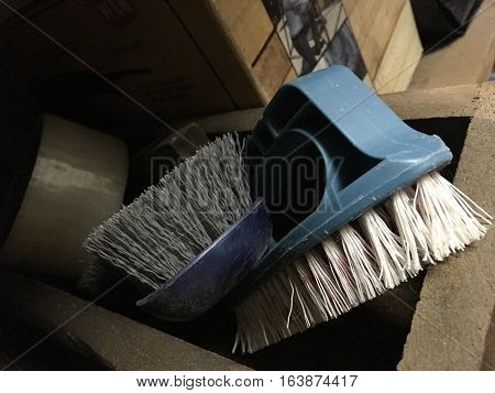 Cleaning brushes in vintage wood box storage shelf in home garage conceptual organization and elbow-grease work background image