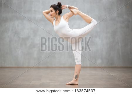 Profile portrait of beautiful young woman wearing white sportswear working out against grey wall, doing yoga or pilates exercise. Standing in Natarajasana, Lord of the Dance pose. Full length