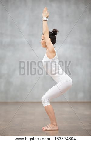 Side view portrait of beautiful young woman wearing white sportswear working out against grey wall, doing yoga or pilates exercise. Standing in Chair, Utkatasana pose. Full length