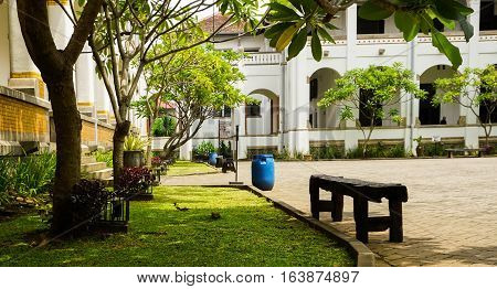 a blue trash can and a wood bench at Lawang Sewu photo taken in Semarang Indonesia java