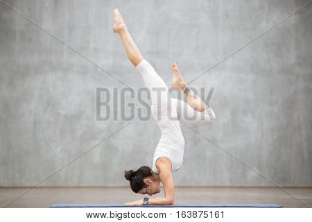 Portrait of attractive young woman with beautiful tattoo working out against grey wall, doing yoga or pilates exercise. Variation of handstand pose, Pincha Mayurasana. Full length photo