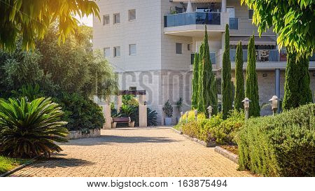 Rishon LeZion Israel-August 19 2016: Pavement backyard walkway to entrance of multi story residential building is flooded by sunset light. This sidewalk is surrounded with green trees and has wooden bench.