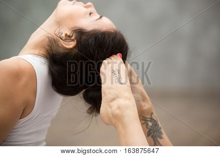 Side view portrait of beautiful young woman with tattoo on her foot meaning Wild kitty working out against grey wall, doing yoga or pilates exercise. King Cobra Pose, Raja bhudjangasana. Close up