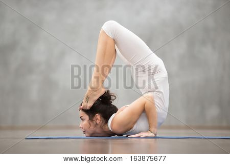 Side view portrait of beautiful young woman with tattoo on her foot meaning Wild kitty working out against grey wall, doing yoga or pilates exercise. Cheststand with backbend. Full length