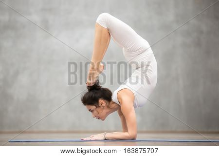 Side view portrait of beautiful slim young woman with tattoo on her foot meaning Wild kitty working out in fitness center, doing yoga or pilates exercise. Scorpion pose, vrischikasana. Full length