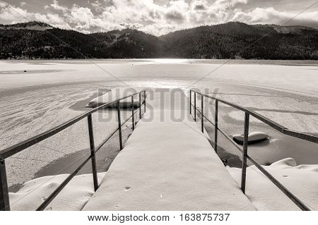 A B&W of a dock on frozen Spirit Lake during winter in Spirit Lake Idaho.