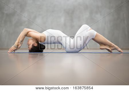 Beautiful young woman wearing white sportswear working out in fitness club against grey wall, doing yoga or pilates exercise. Variation of Matsyasana, Fish pose with crossed arms and legs. Full length