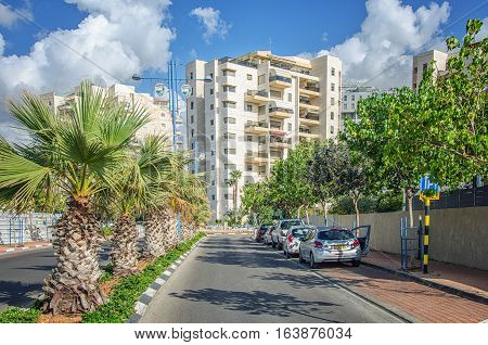 Rishon LeZion Israel-May 27 2016: Little green Ahi Hets Street is surrounded palms from one side and trees from other. Some private cars are parked. There are white 9-story residential buildings in blue sky background