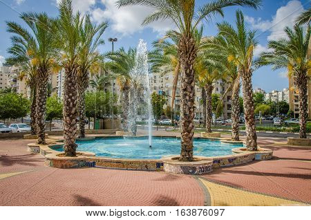 Rishon LeZion Israel-May 28 2016: Mosaics octagonal fountain is surrounded palm trees growing in each corner. Wide shot is taken on multi-story residential buildings background with blue sky
