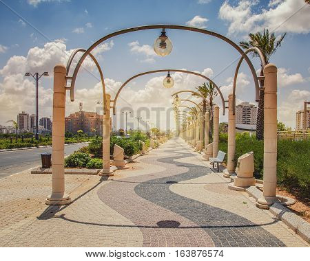 Sidewalk with semi-circular metal street light poles in Rishon LeZion. They are located above three colored pavement in Henry Kissinger Street in Prize Nobel neighborhood