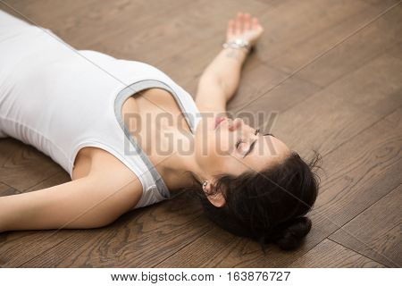 Side view portrait of beautiful young woman working out on wooden floor, resting after doing yoga exercises, lying in Shavasana Corpse or Dead Body Posture , relaxing. Face close up