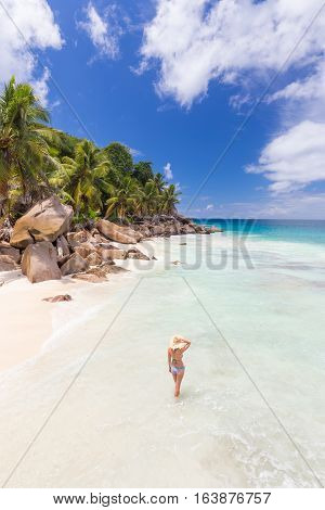 Woman wearing retro striped bikini and beach hat, enjoying amazing view on Anse Patates beach on La Digue Island, Seychelles. Summer vacations on picture perfect tropical beach concept.