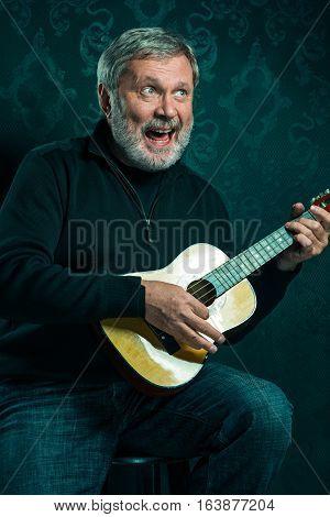 Studio portrait of senior man with small guitar on black studio background