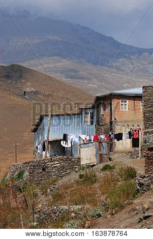 Xinaliq, Azerbaijan - August 23, 2014. Residential house in Xinaliq village, with linen put out to dry and mountains in the background.