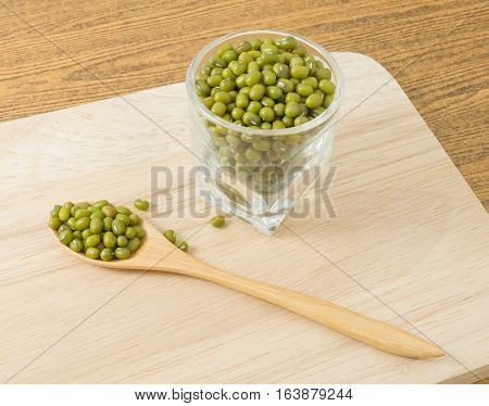 Cuisine and Food Raw and Uncooked Mung Dried Beans in A Wooden Spoon and A Tumbler on Wooden Cutting Board.