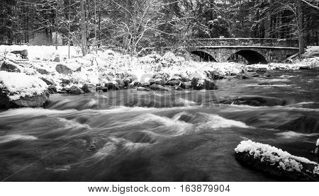 Black and white winter river landscape with stone bridge in background
