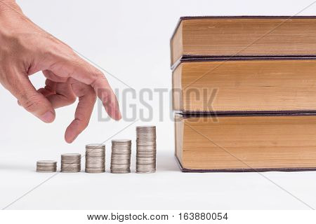 A Man Hand Running Up On Coins To The Books, Invest In Education Of Diploma And University Student L