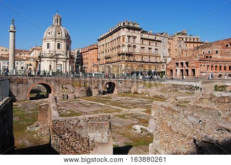 Rome, Italy - October 9, 2014. View of Trajan Forum in Rome, with Roman ruins, Trajan Column, Chiesa SS Nome di Maria, surrounding buildings and people.