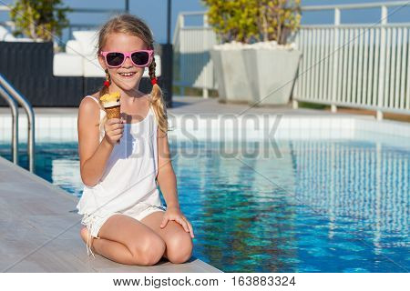 Happy Little Girl With Ice Cream Sitting Near A Swimming Pool At The Day Time.
