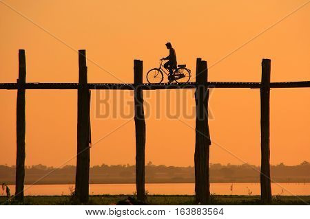 Silhouetted Person On With A Bike On U Bein Bridge At Sunset, Amarapura, Myanmar