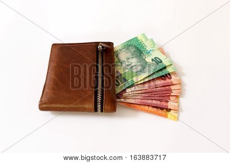 South African Rand in wallet sticking out of a wallet on a white canvas