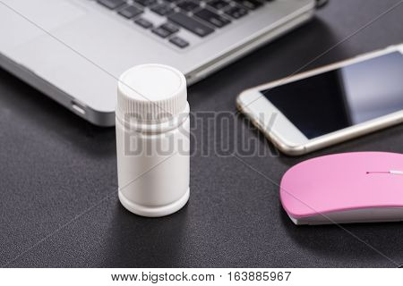 Medicine Bottle With Laptop And Smartphone On Black Table, Close Up.