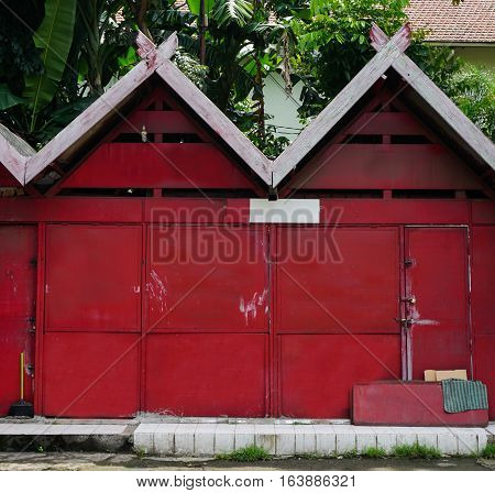 Red store house with green garden inside photo taken in Semarang indonesia java