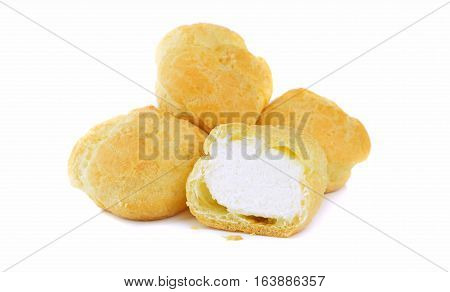 A pile of fresh cream puff pastries on a white background