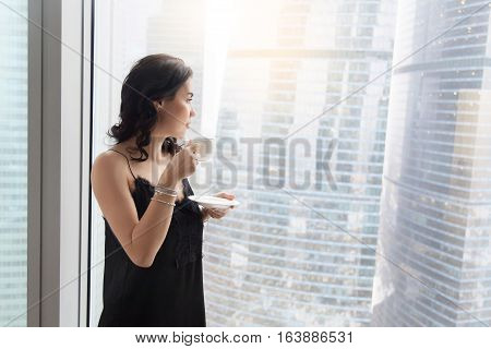 Profile view of calm young woman standing near window with cup of coffee, looking through glass wall at city after waking up in the morning, resting, dreaming before starting working day. Copy space