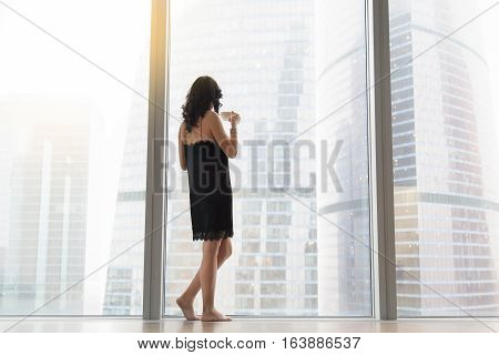Full length rear view of a young woman standing near the window with a cup of coffee, looking at the city after waking up in the morning, wearing nightwear, detaching from work, welcoming a new day