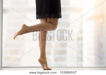 Female bare legs, staying on tiptoe, healthy legs, smooth skin, helping mind and body relax and rejuvenate after work, taking dancing classes, exercising at morning at window with city view. Close up