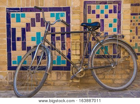 Bycicle near the wall with traditional floral mosaic decoration Bukhara Uzbekistan 2016