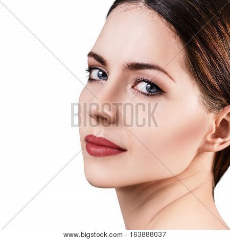 Beautiful woman with healty fresh skin looking around over white background. Spa concept.