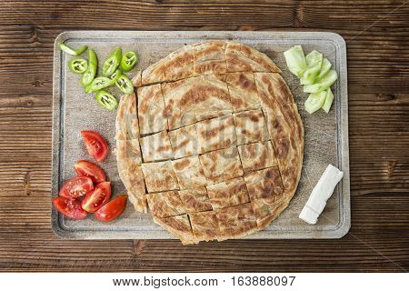 Traditional Turkish Borek Served With Tomatoes,Peppers, Cheese And Sliced Cucumbers