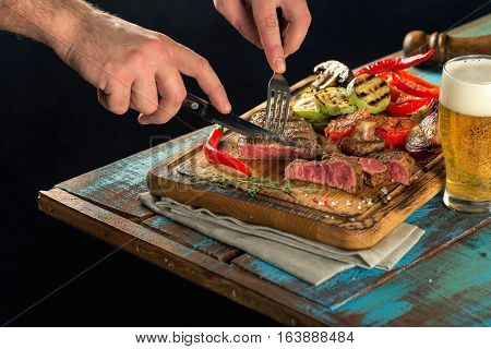Man dinner steak grilled with grilled vegetables and a glass of lager beer