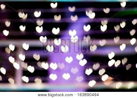 Defocused lights background. Heart bokeh. Bright colorful heart bokeh background. Multicolored blurry hearts on a black background.
