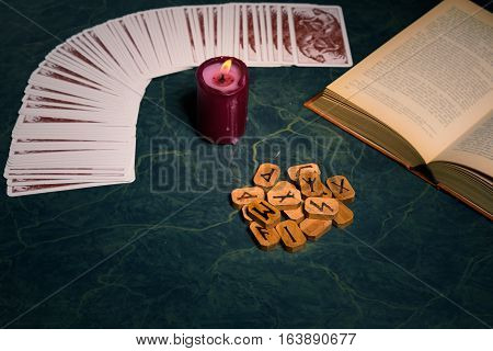 Composition of esoteric objectscandleCardsbook and wooden runes used for healing and fortune-tellingon green backgroundvintage style.